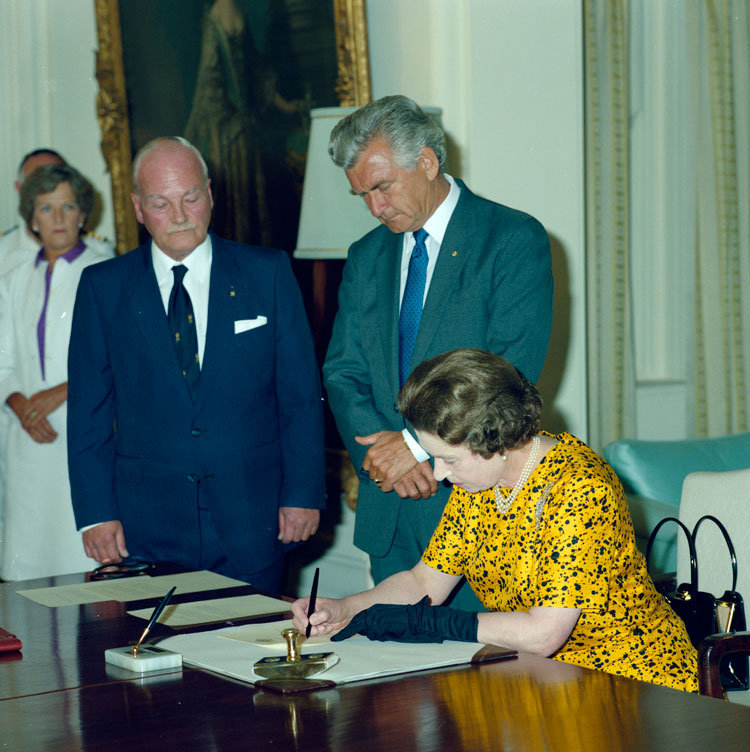 Queen Elizabeth II signs her Assent to the Australia Act on 2 March 1986 at Government House