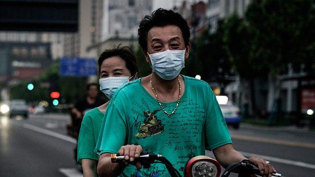 People on bike wearing face mask