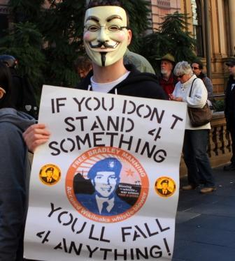 """Photo of masked man with poster """"If you don't stand 4 something, you'll fall 4 anything."""""""